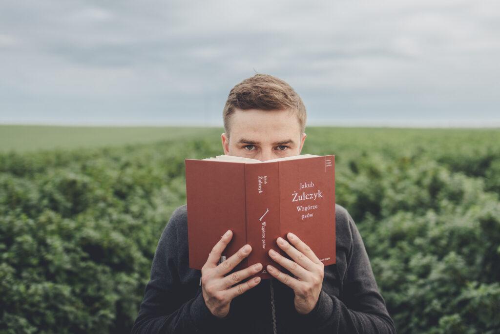 mężczyzna na polu trzyma książkę w rękach