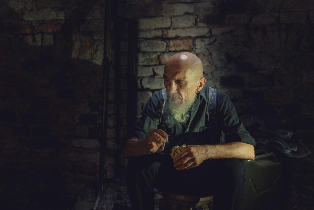 zmęczony mężczyzna z brodą siedzi z papierosem w ręku