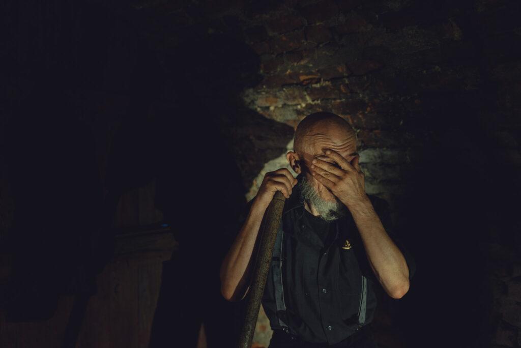 zmęczony mężczyzna przeciera twarz ręką