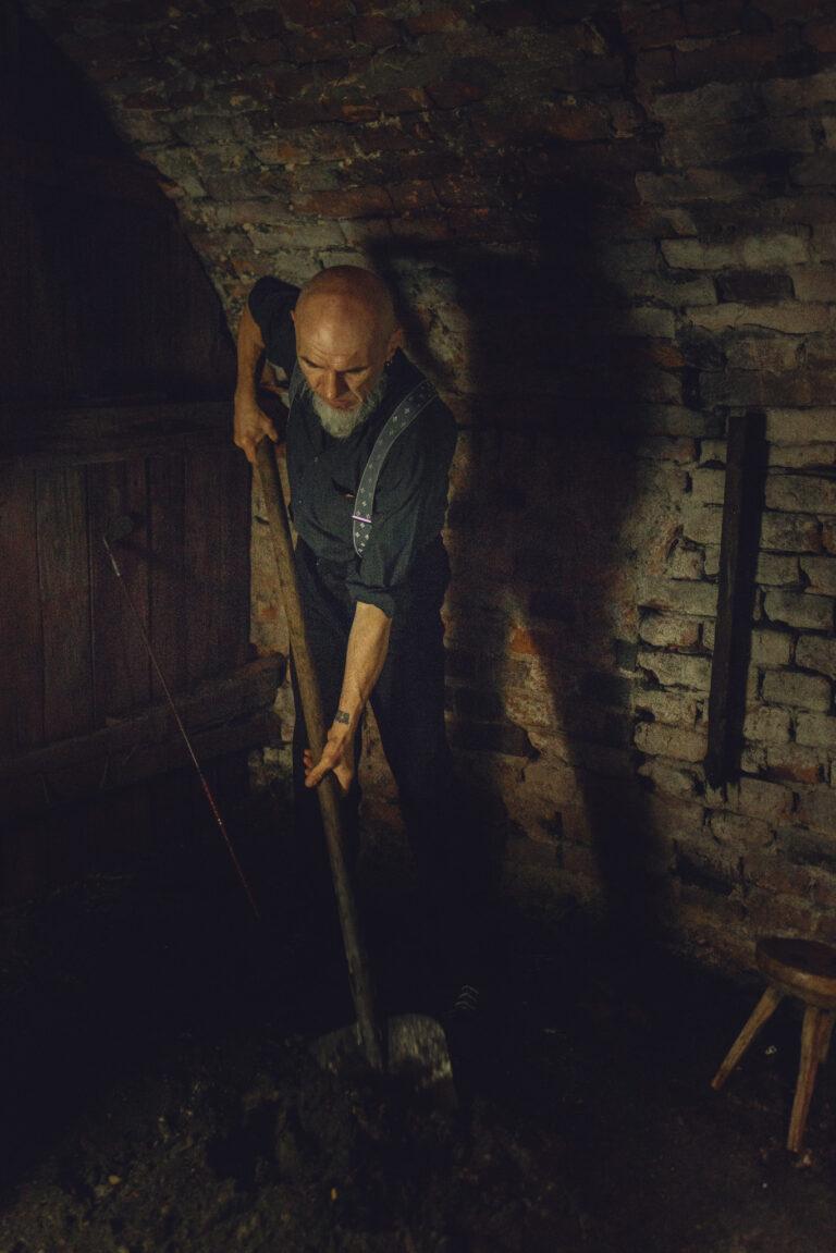 mężczyzna z łopatą, zakopujący coś w lochu