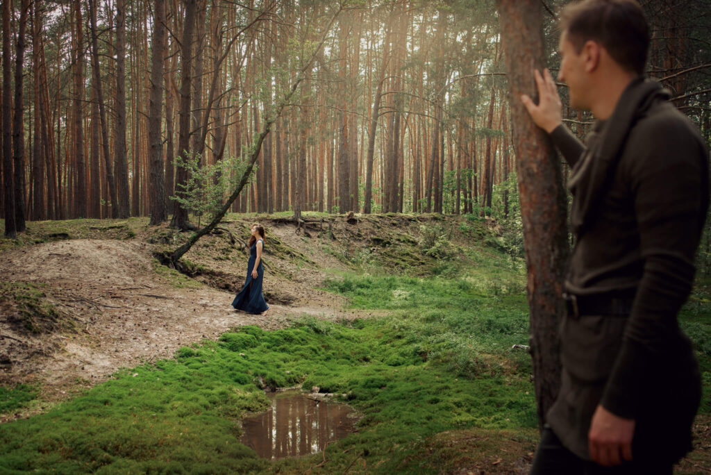 lady in blue dress and a man standing in a forest